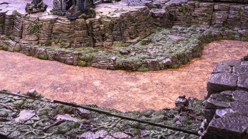 A dry riverbed banked with forest ledges