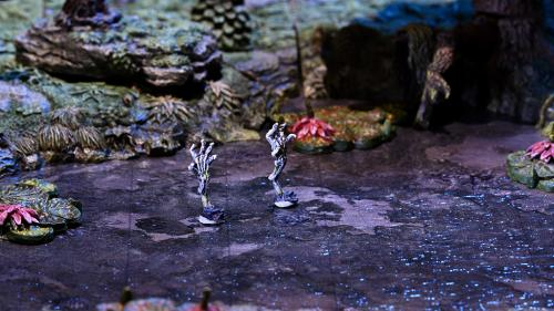 Skeletal hands rise from the swamp mire.