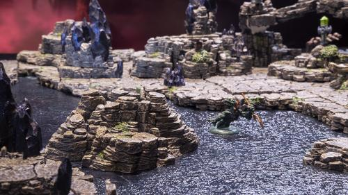 The lizardfolk returns to the mountain pool after leaving the mountain's expansive cliffs